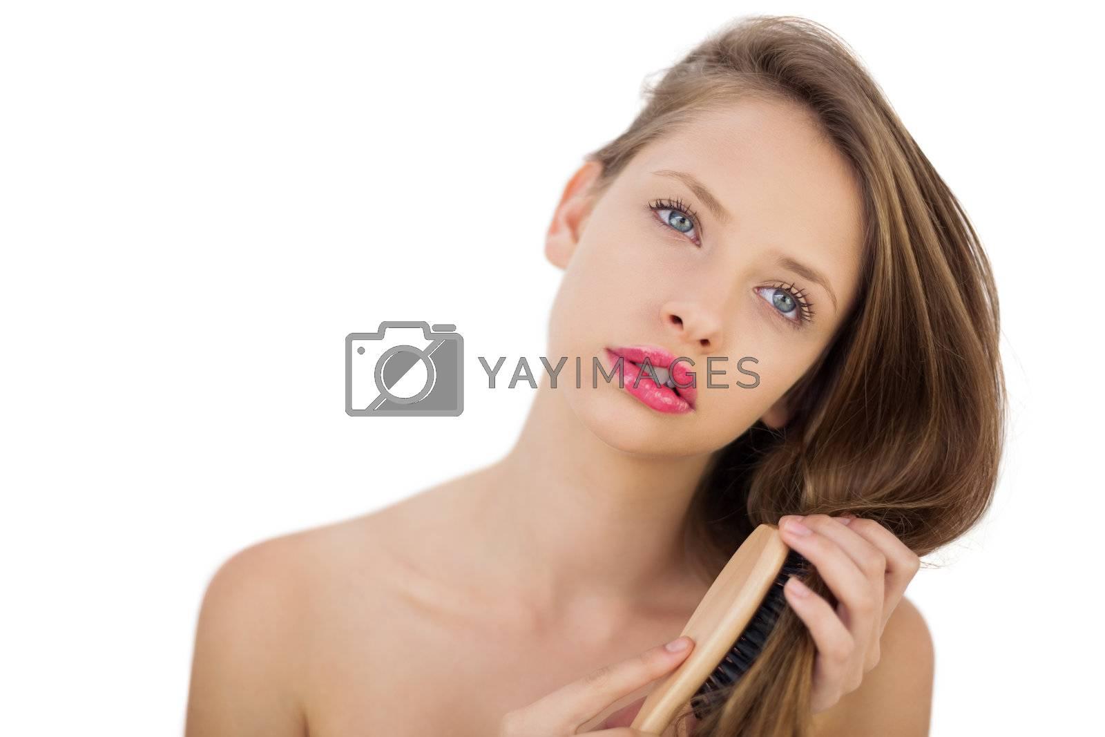 Thoughtful brunette model brushing her hair by Wavebreakmedia