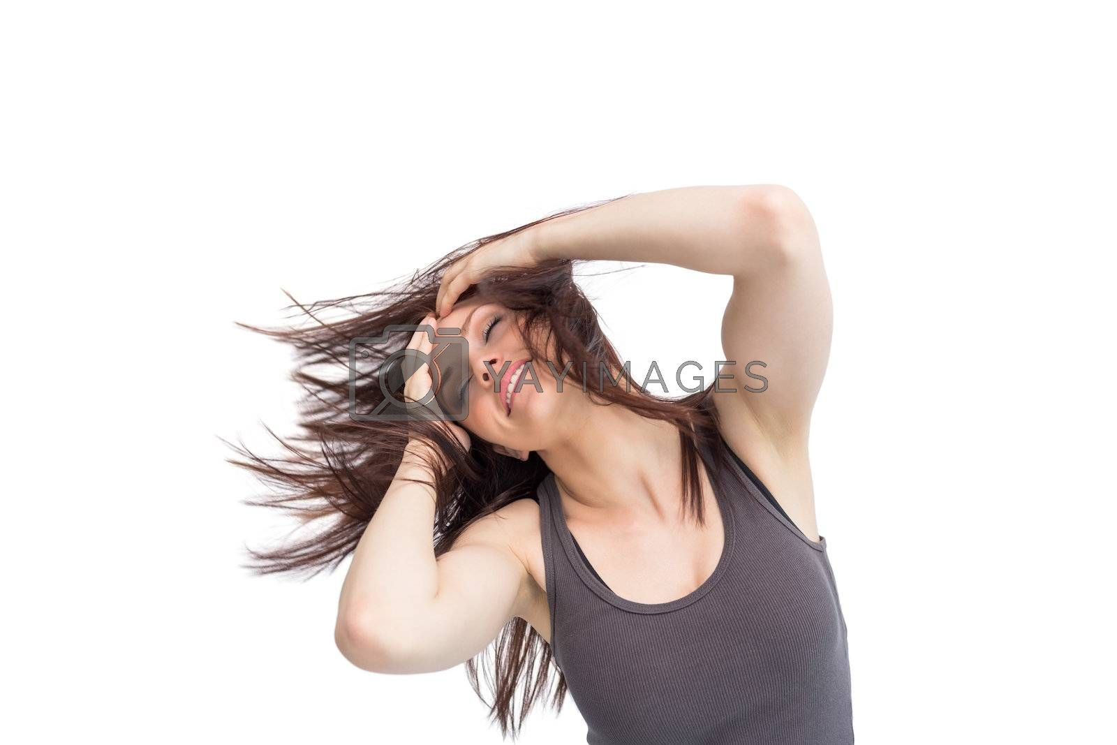 Pretty young brunette tossing her hair by Wavebreakmedia