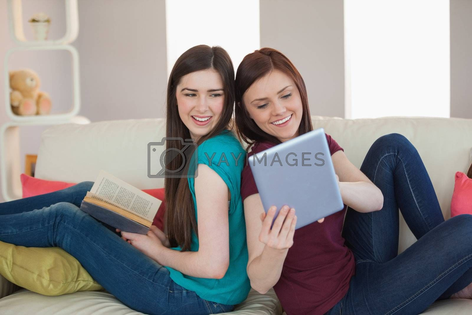 Girl showing her friend her tablet pc on the sofa by Wavebreakmedia