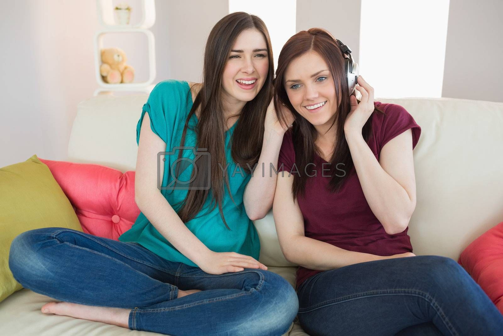 Smiling girl listening to music with her friend beside her on the sofa by Wavebreakmedia