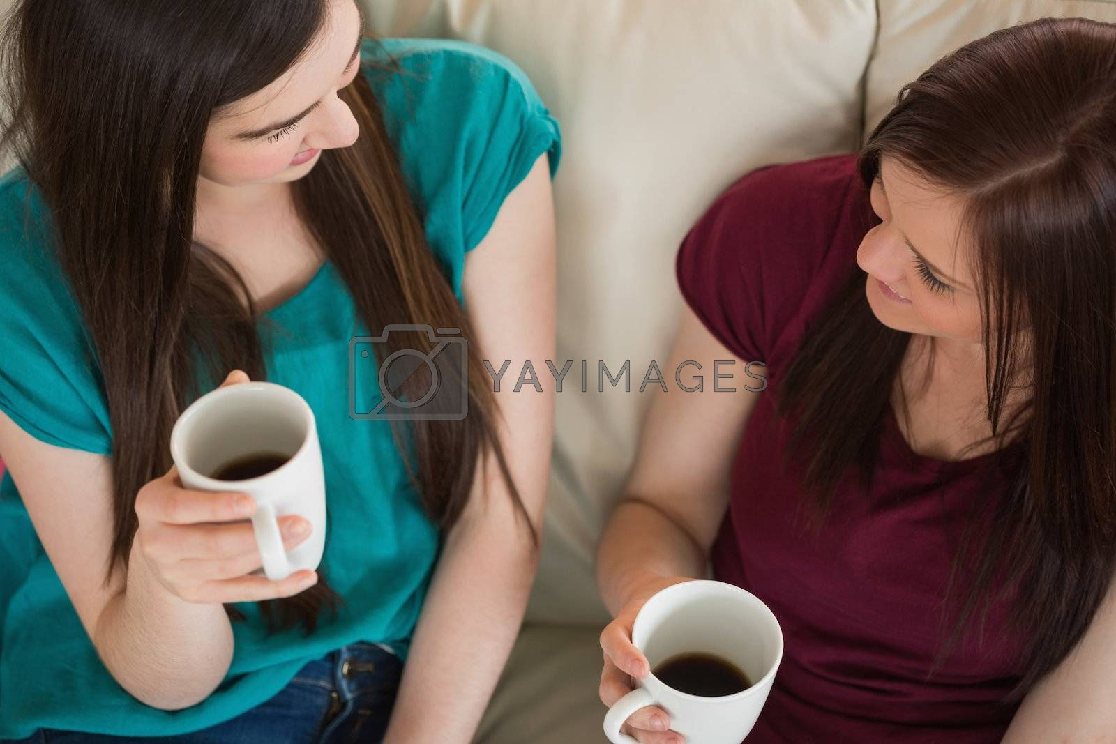 Two smiling friends having coffee and chatting on the couch by Wavebreakmedia