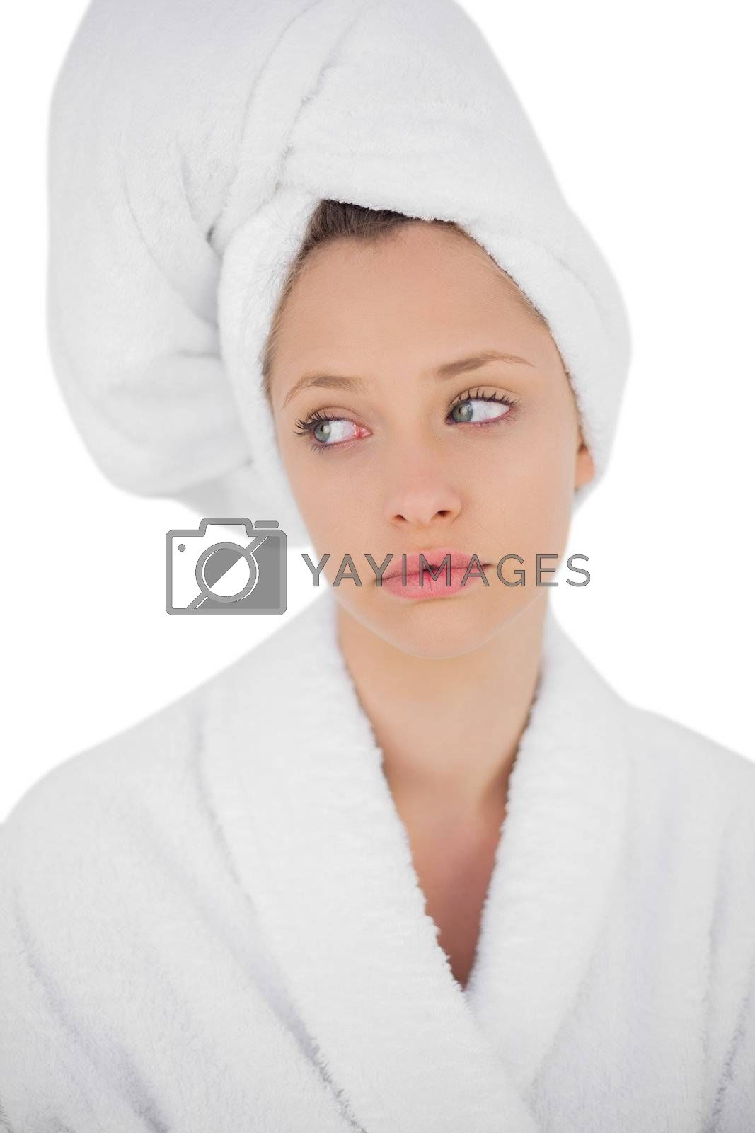 Thinking brunette in bathrobe looking away by Wavebreakmedia