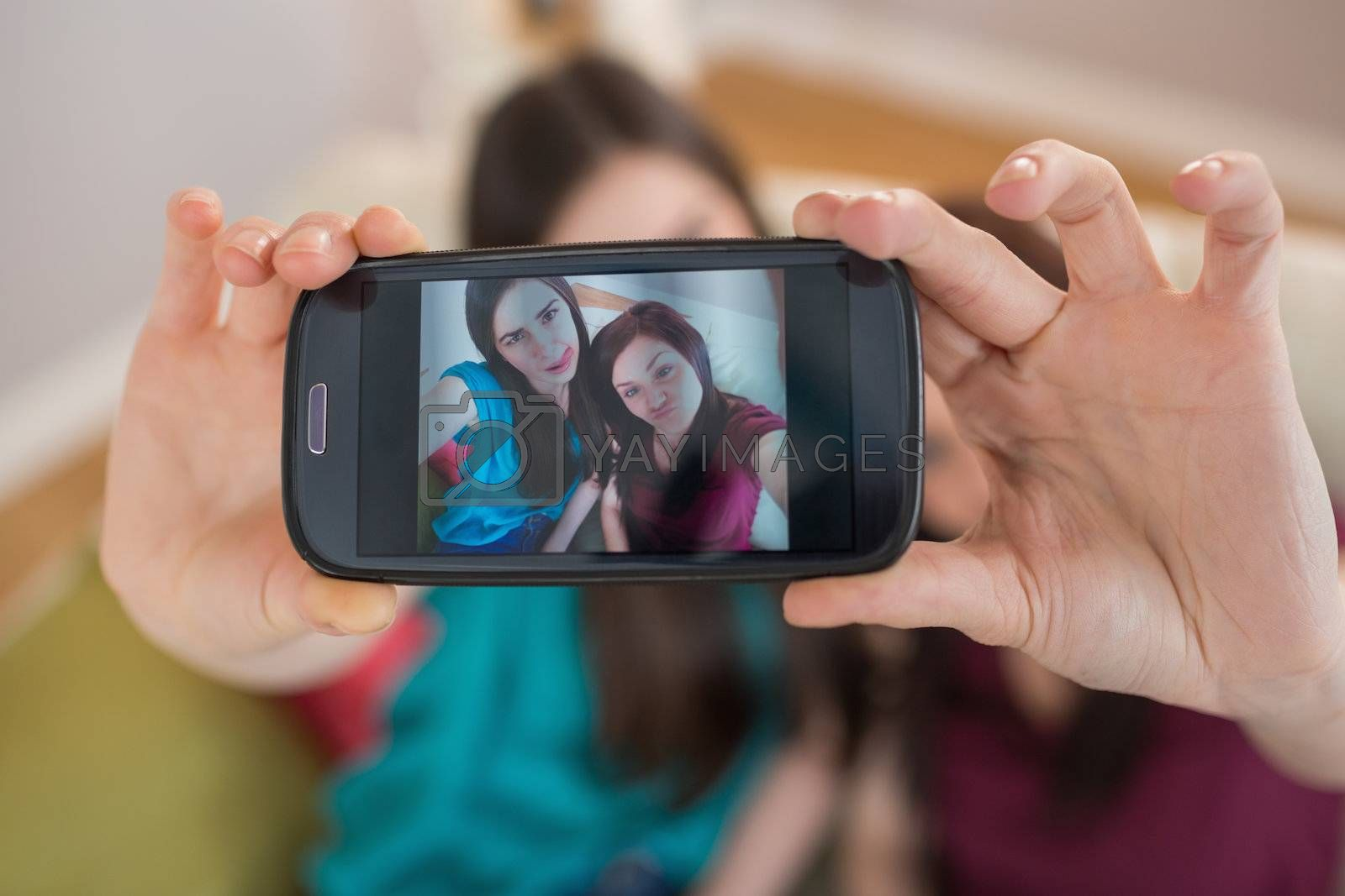 Two happy friends on the couch taking a selfie with smartphone by Wavebreakmedia