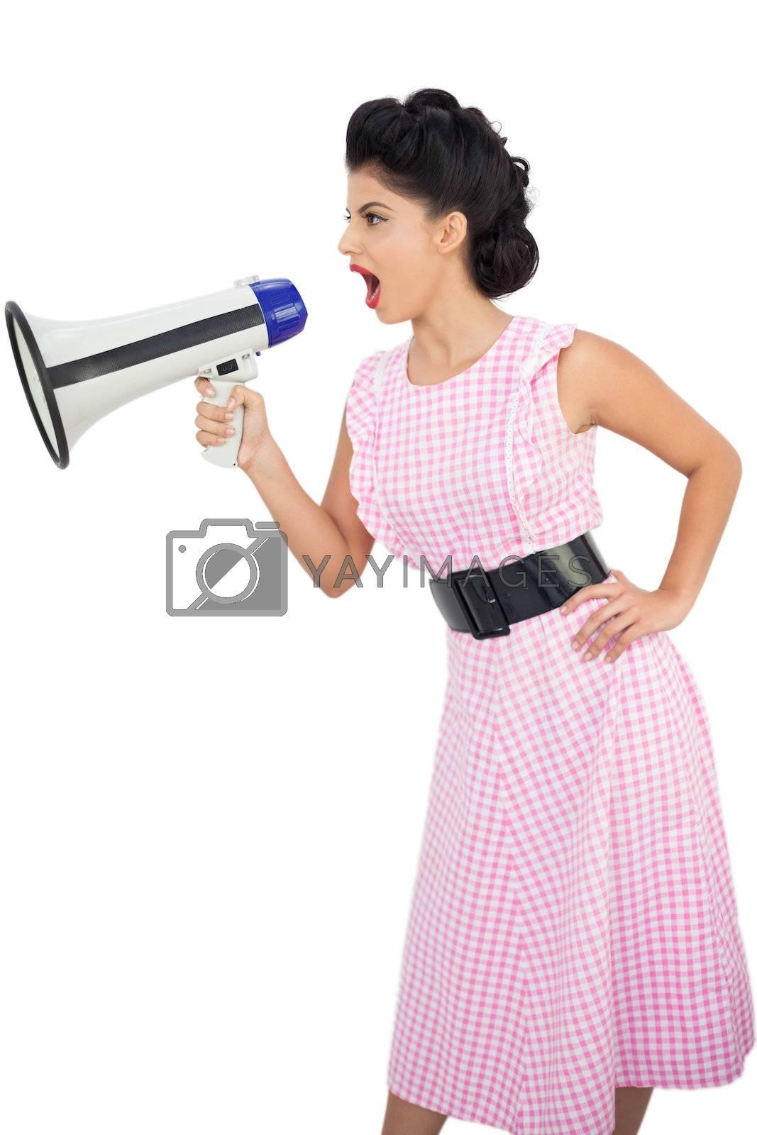 Angry black hair model shouting in a megaphone by Wavebreakmedia