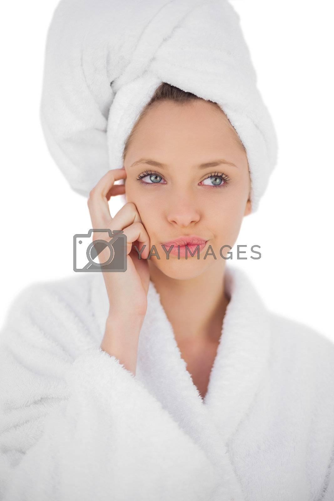Content brunette in bathrobe looking away by Wavebreakmedia