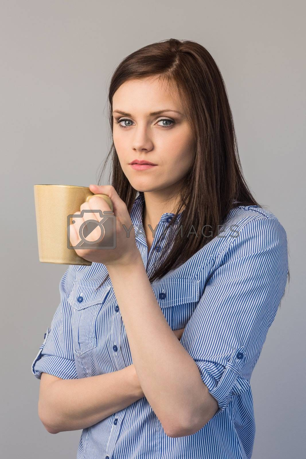 Serious pretty brunette holding cup of coffee by Wavebreakmedia