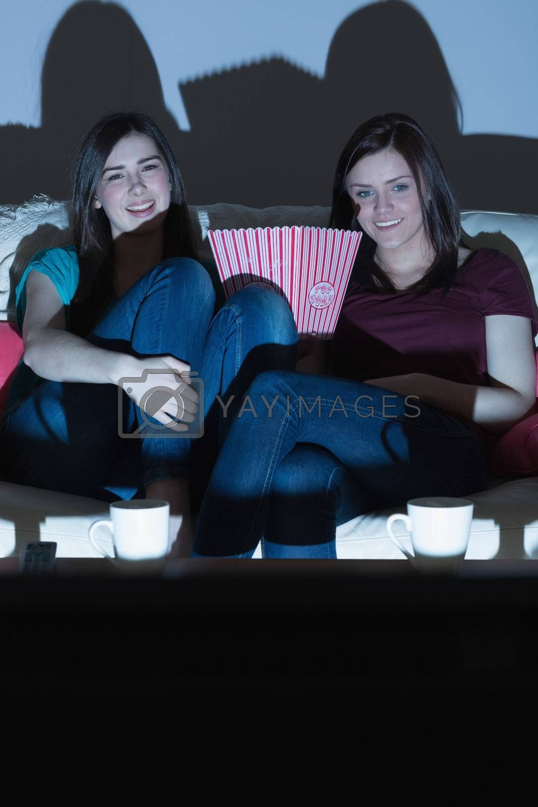 Two smiling friends on the couch watching tv together in the dark by Wavebreakmedia