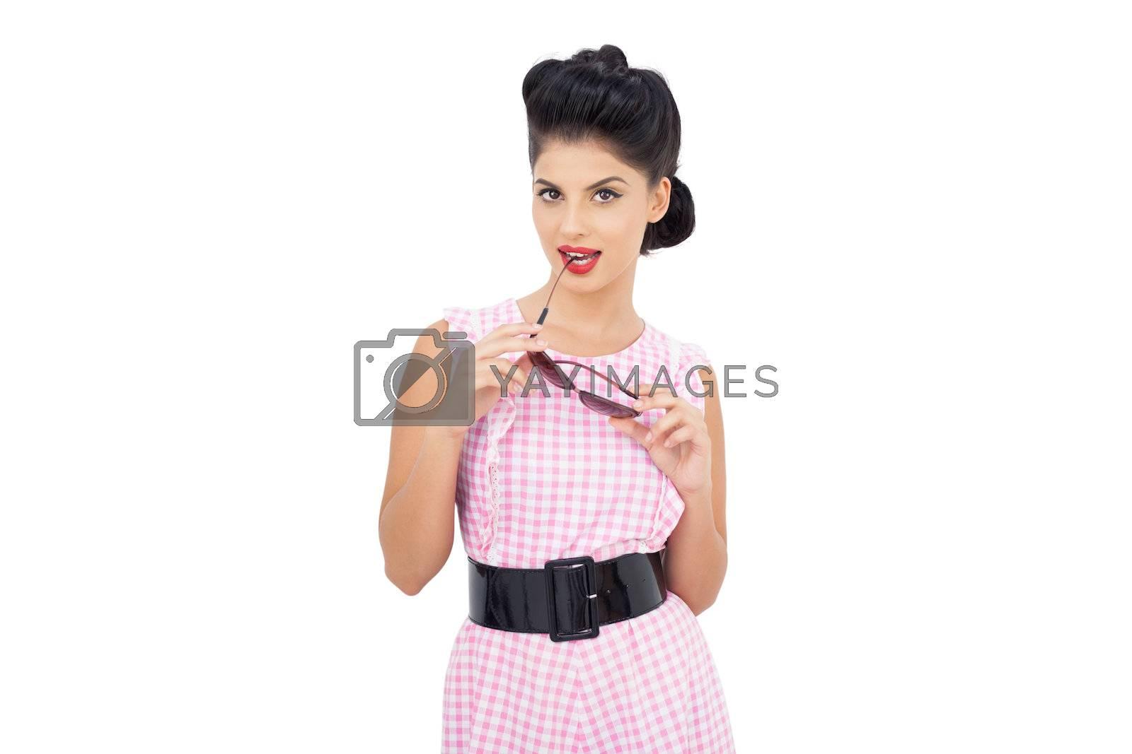 Seductive black hair model chewing her sunglasses by Wavebreakmedia
