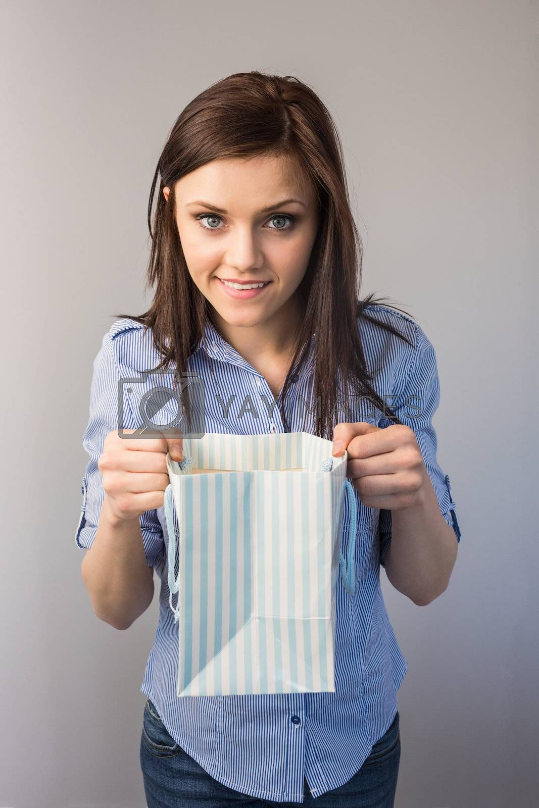 Cheerful pretty brunette receiving a present by Wavebreakmedia