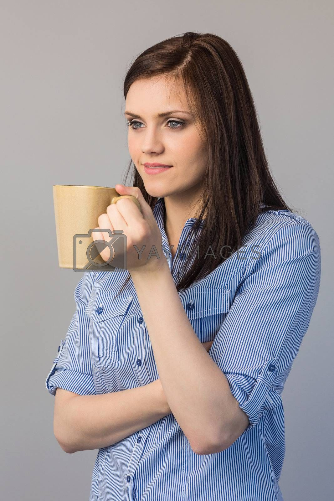 Pensive pretty brunette holding cup of coffee by Wavebreakmedia