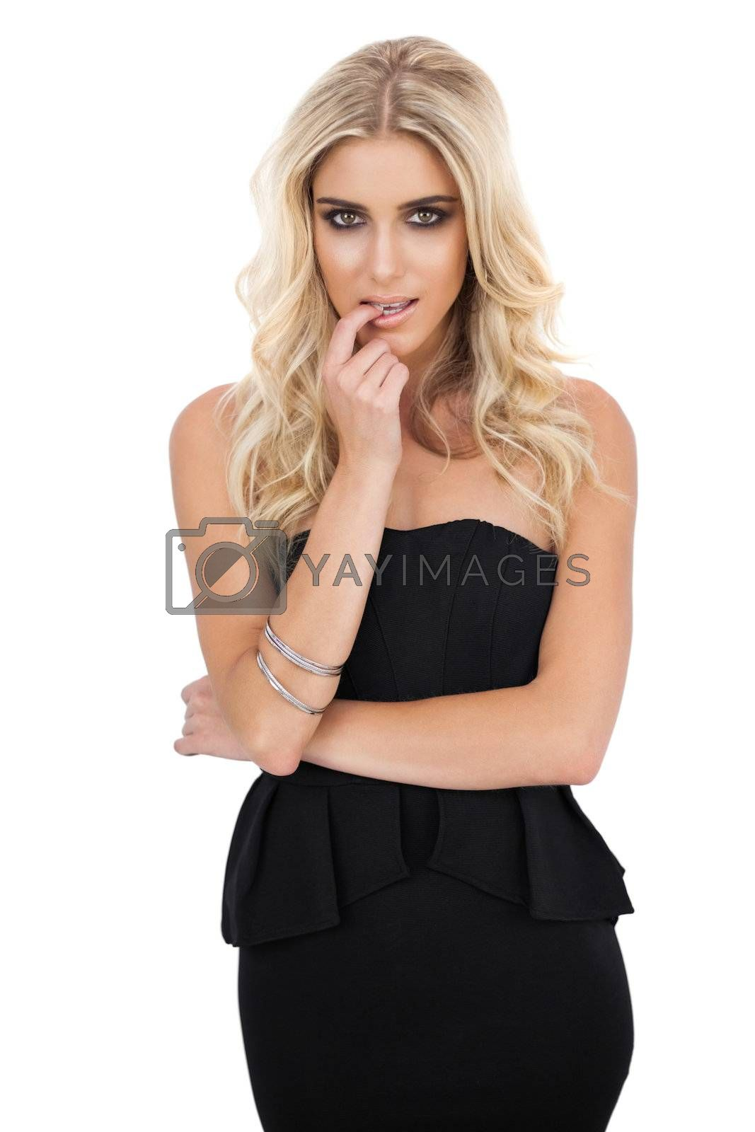 Thoughtful blonde model in black dress posing a finger in the mouth by Wavebreakmedia