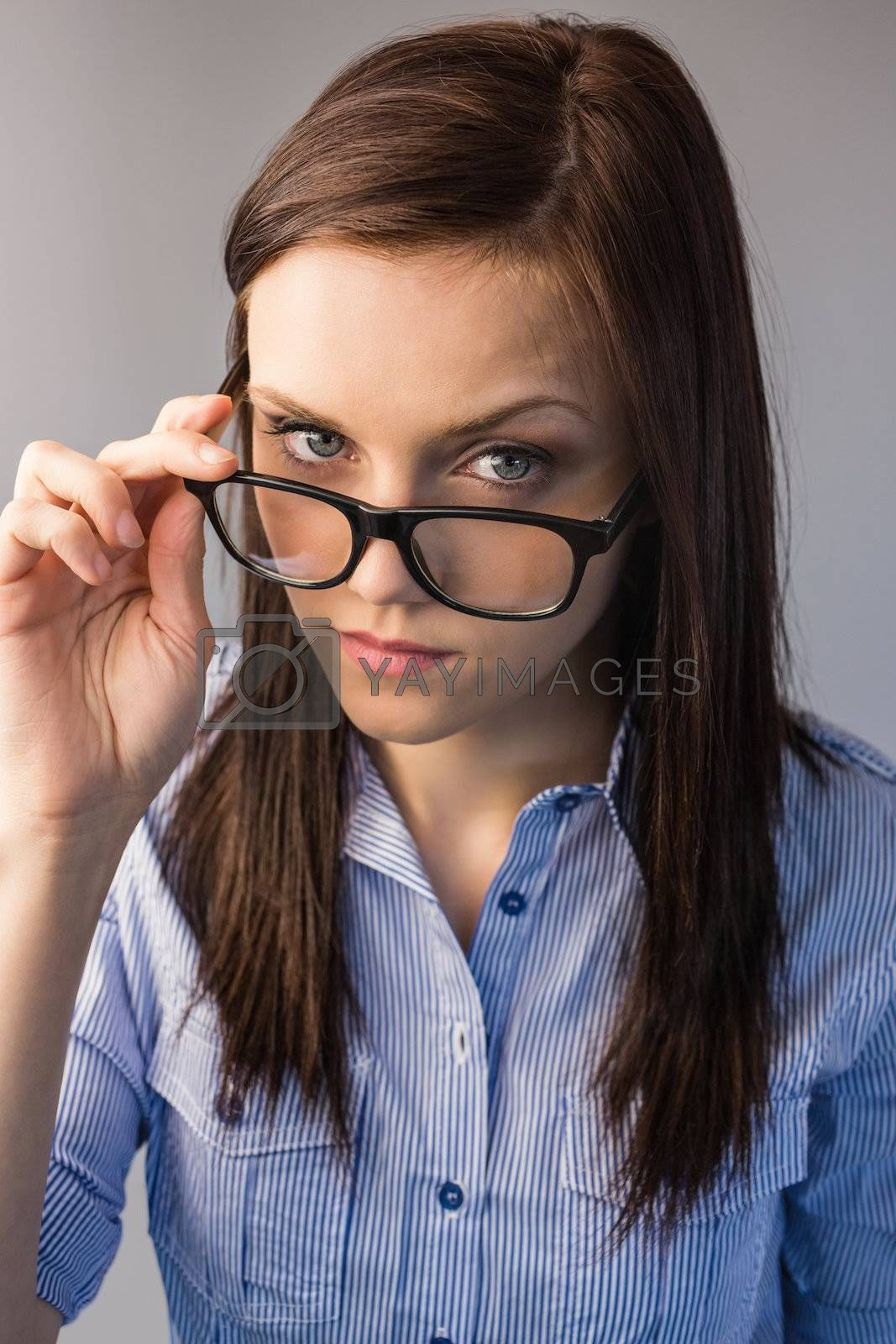 Serious brunette holding glasses posing by Wavebreakmedia
