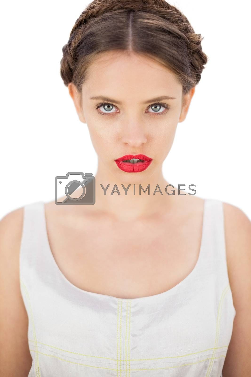 Concentrated model in white dress posing looking at camera by Wavebreakmedia