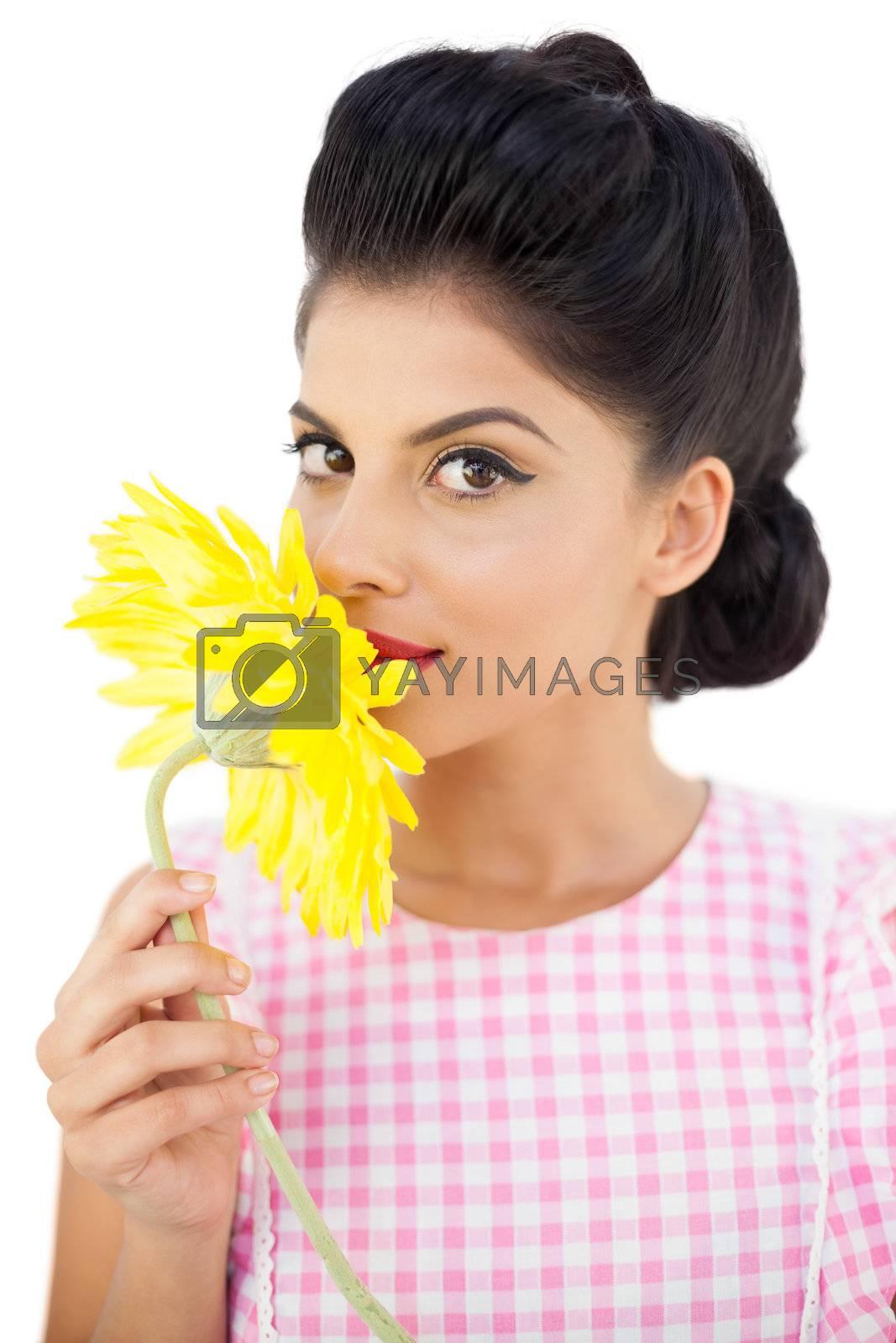 Seductive black hair model smelling a flower by Wavebreakmedia