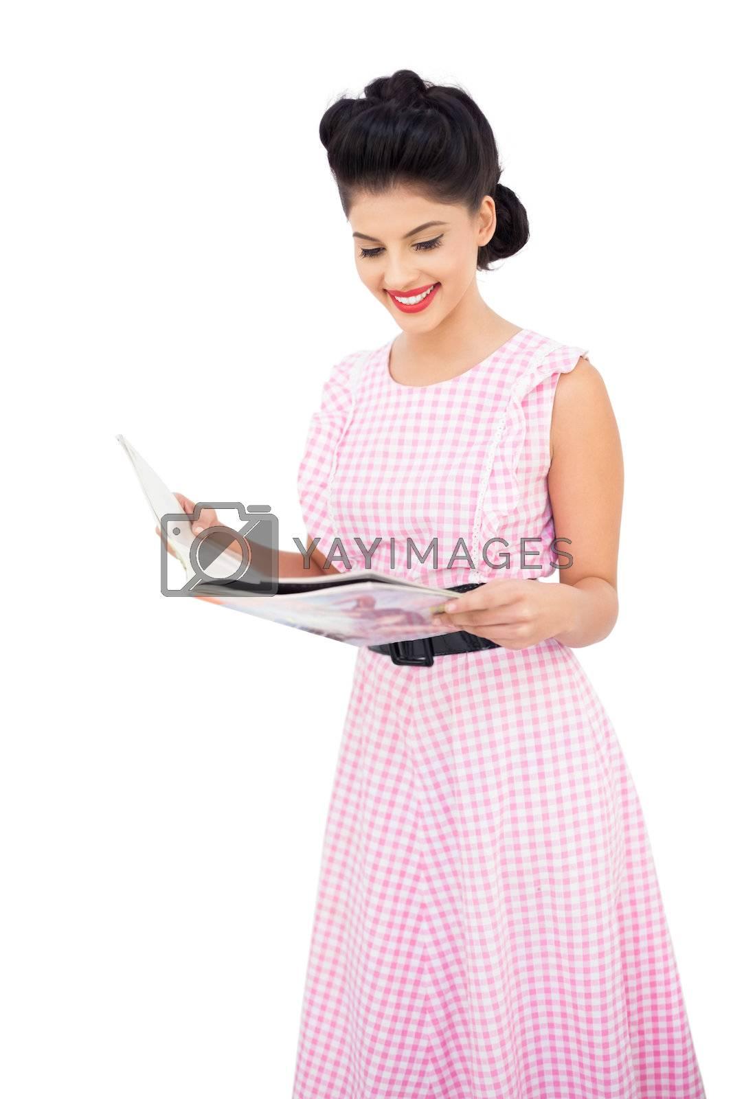 Smiling black hair model reading a magazine by Wavebreakmedia