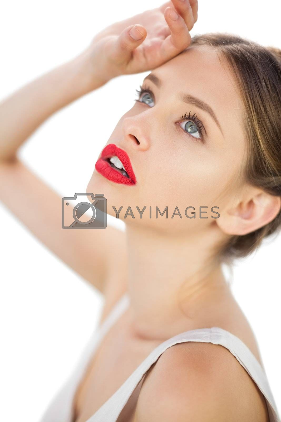 Elegant model in white dress posing with a hand on her forehead by Wavebreakmedia