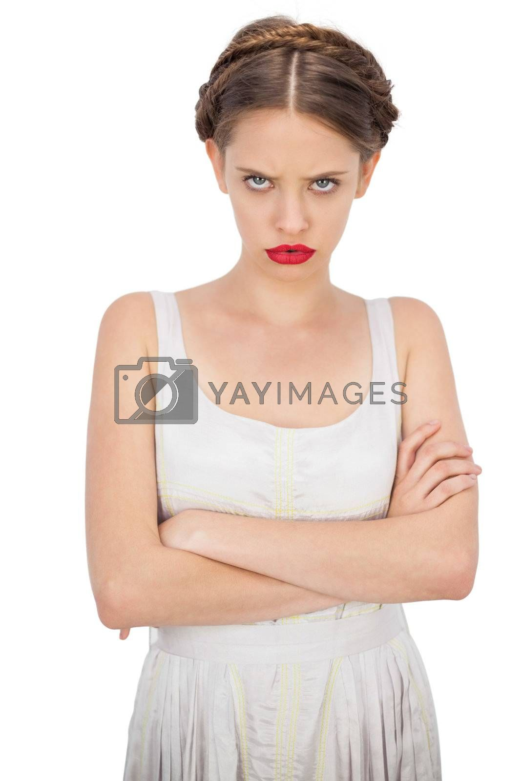 Frowning model in white dress posing with crossed arms by Wavebreakmedia