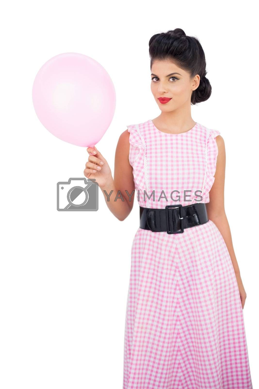 Pleased black hair model holding a pink balloon by Wavebreakmedia