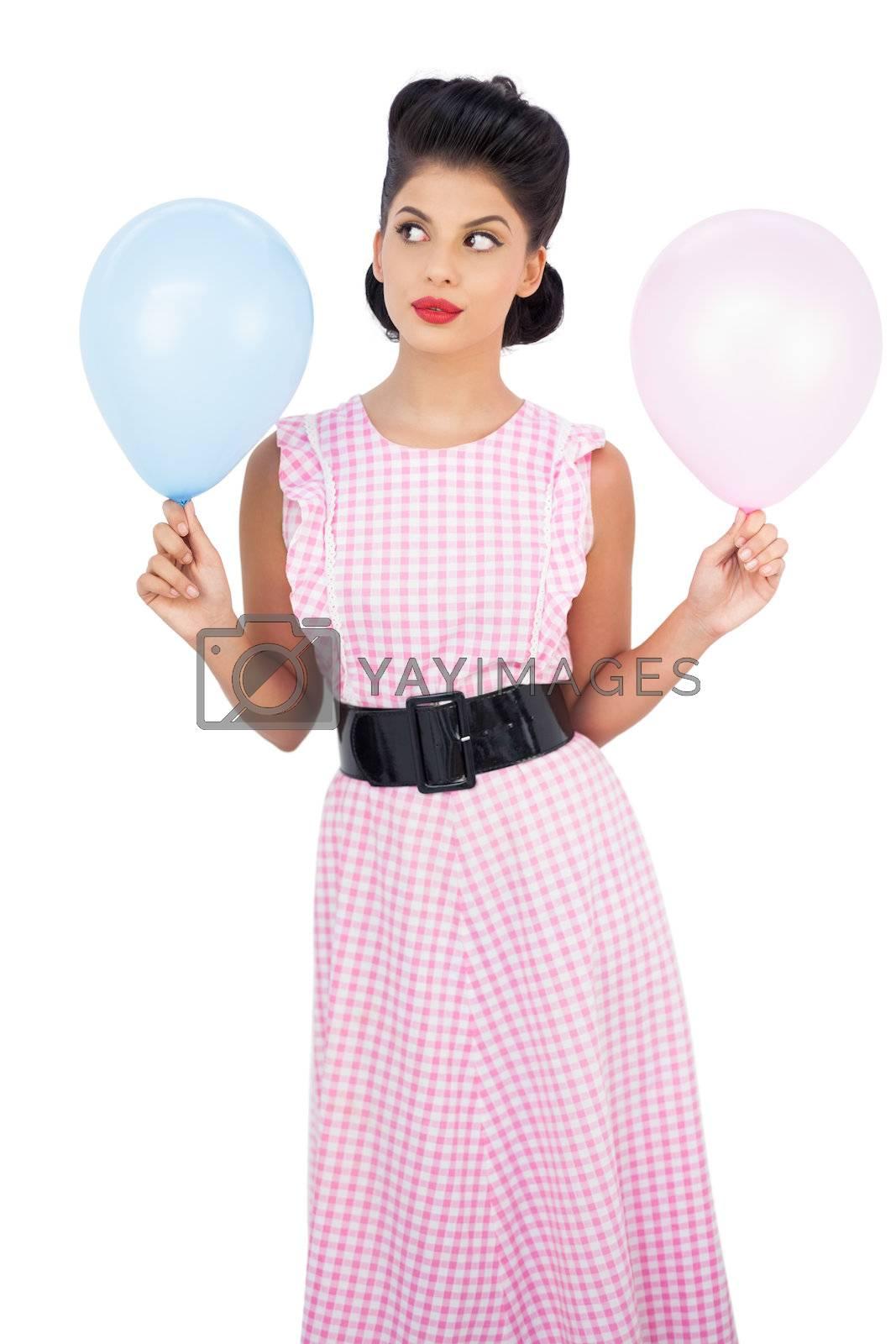 Thoughtful black hair model holding balloons by Wavebreakmedia