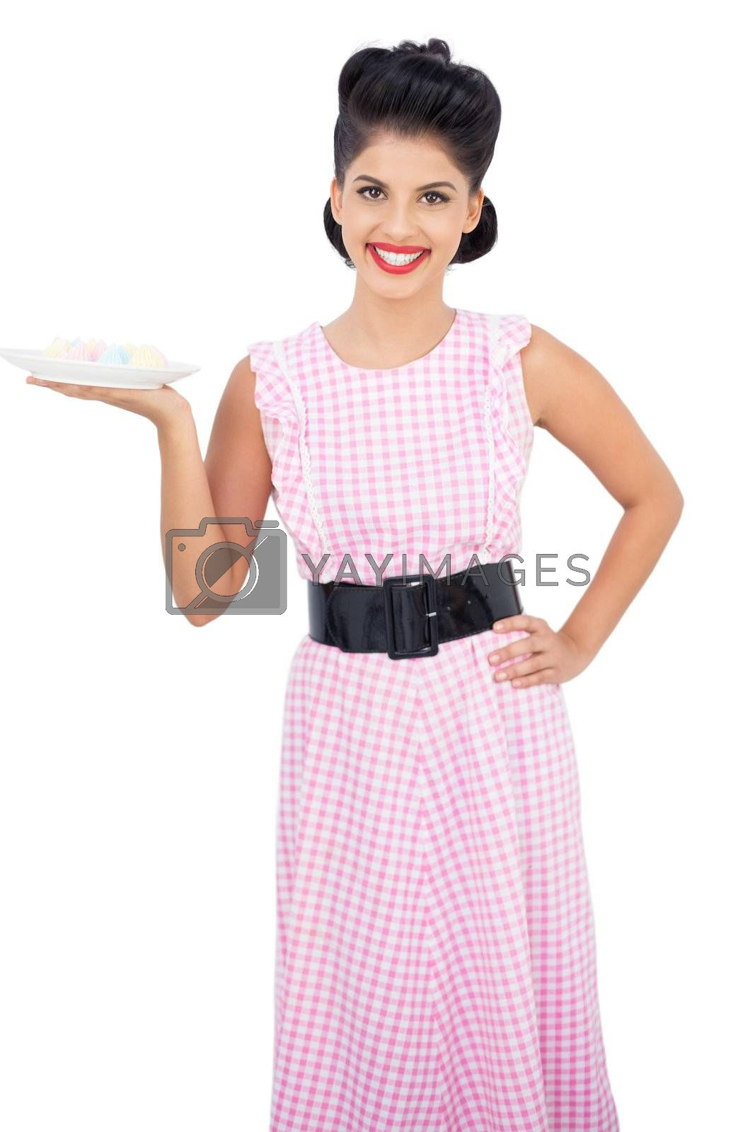Joyful black hair model holding a plate of candies by Wavebreakmedia