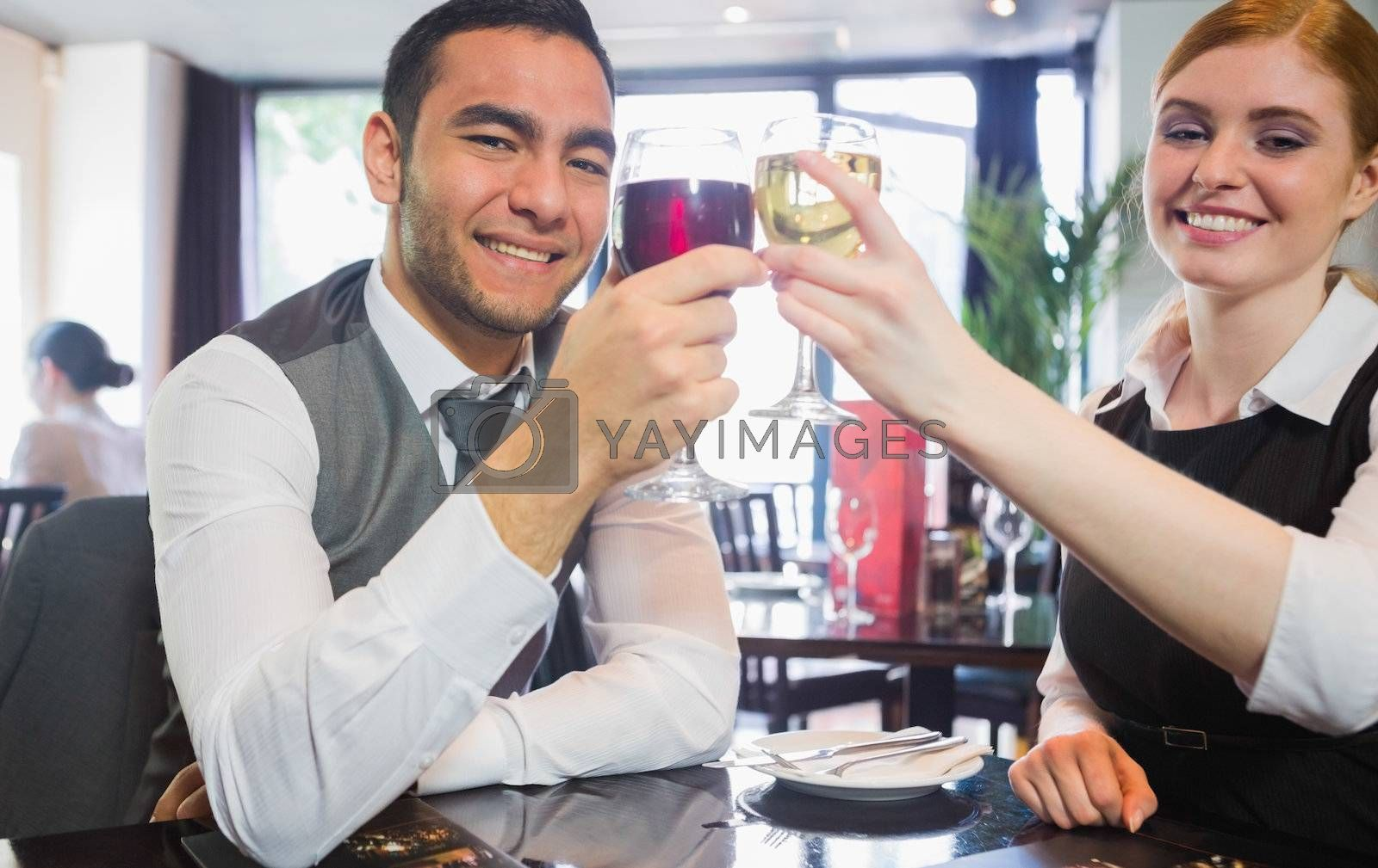 Smiling business partners clinking wine glasses looking at camera in a restaurant