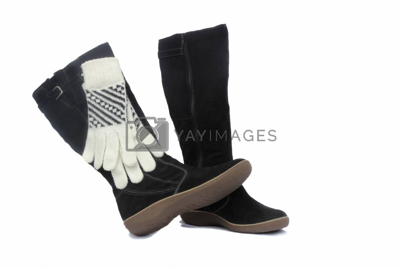 Winter suede black boots and white with black ornament gloves. Presented on a white background.