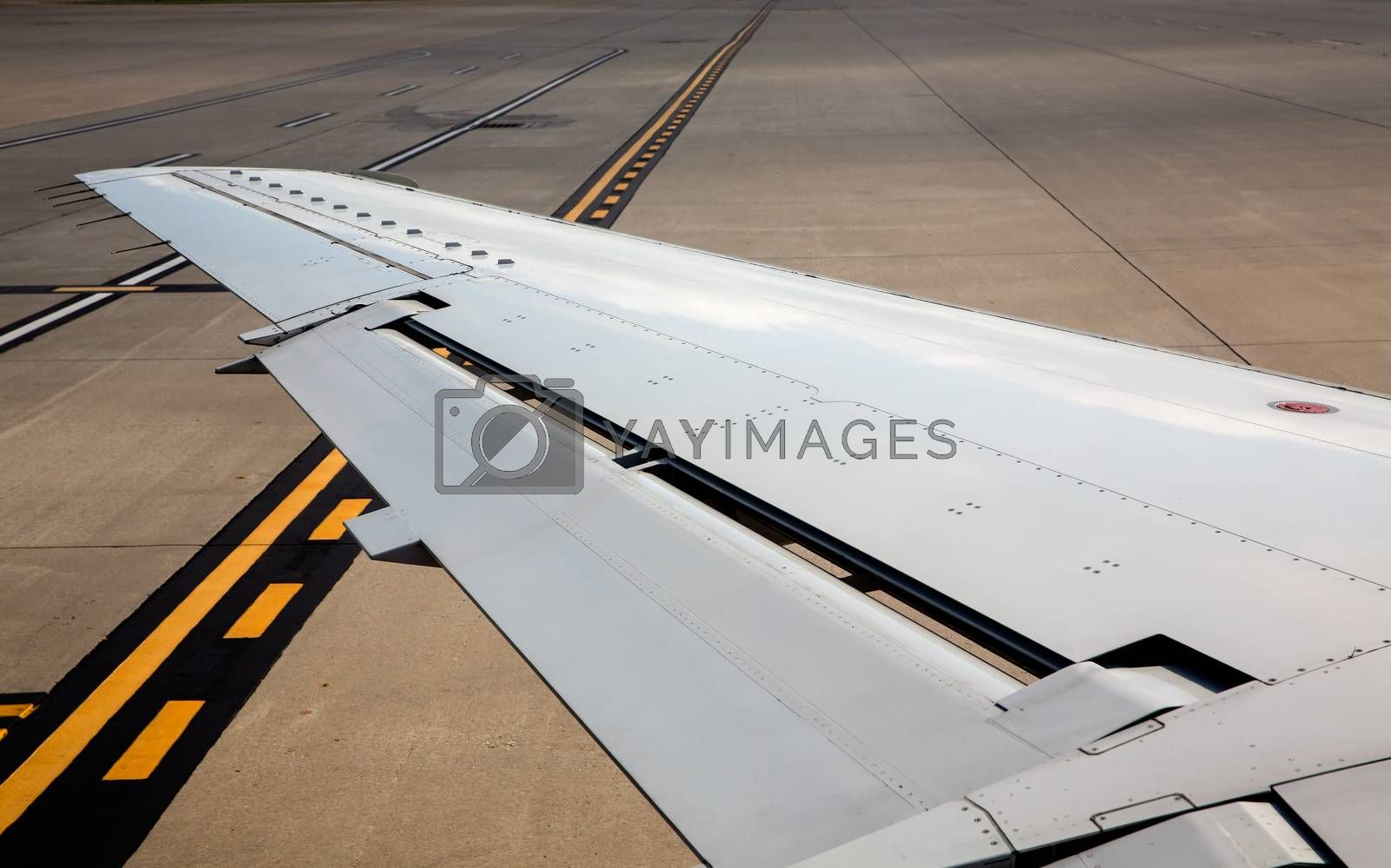 aircraft airplane left wing on airport soil painted signs