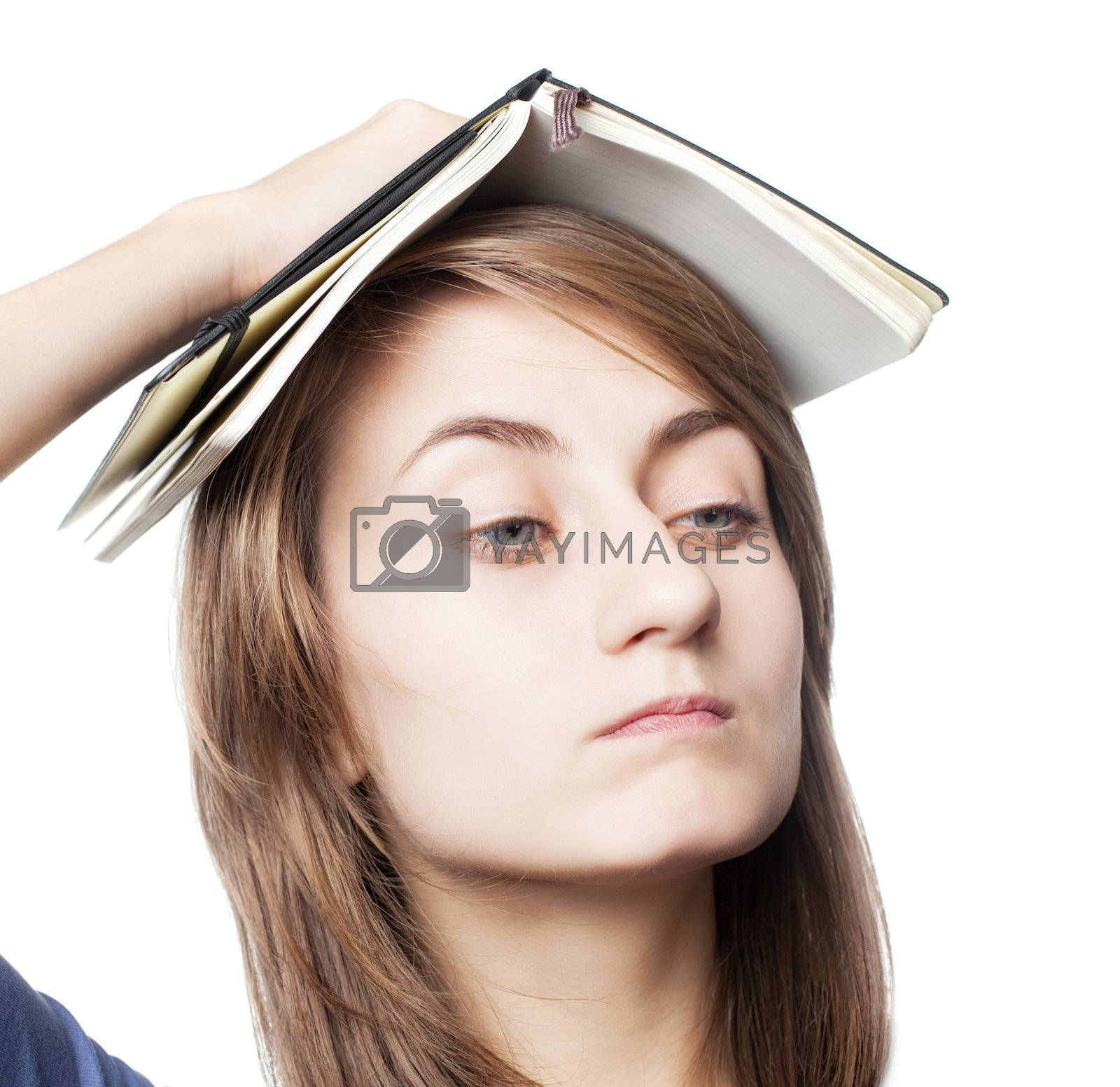 Education. Tired girl holds a notebook on her head on a white background