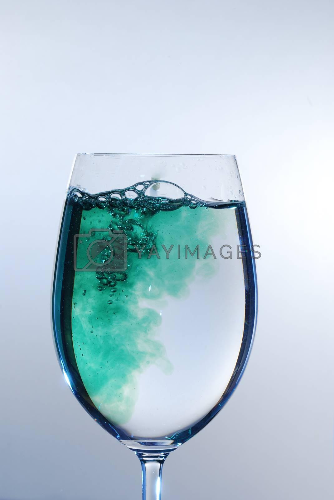 green bubbling liquid in a wine glass