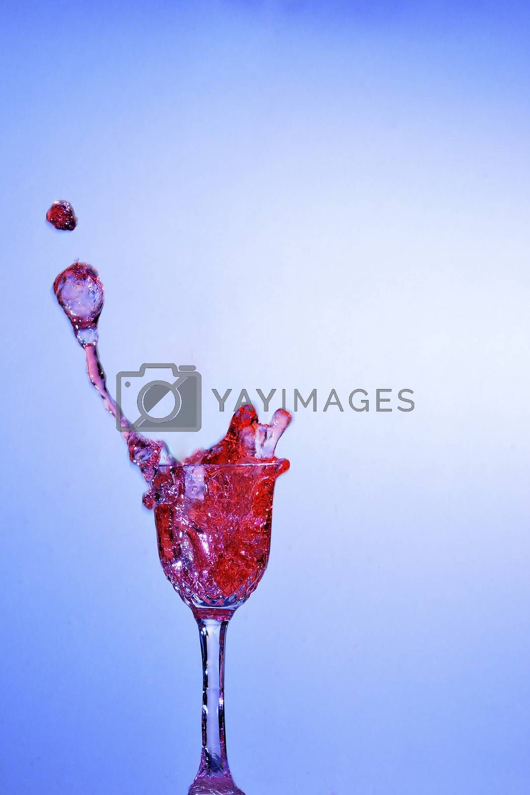 red liquid bubbling in a small glass with blue background