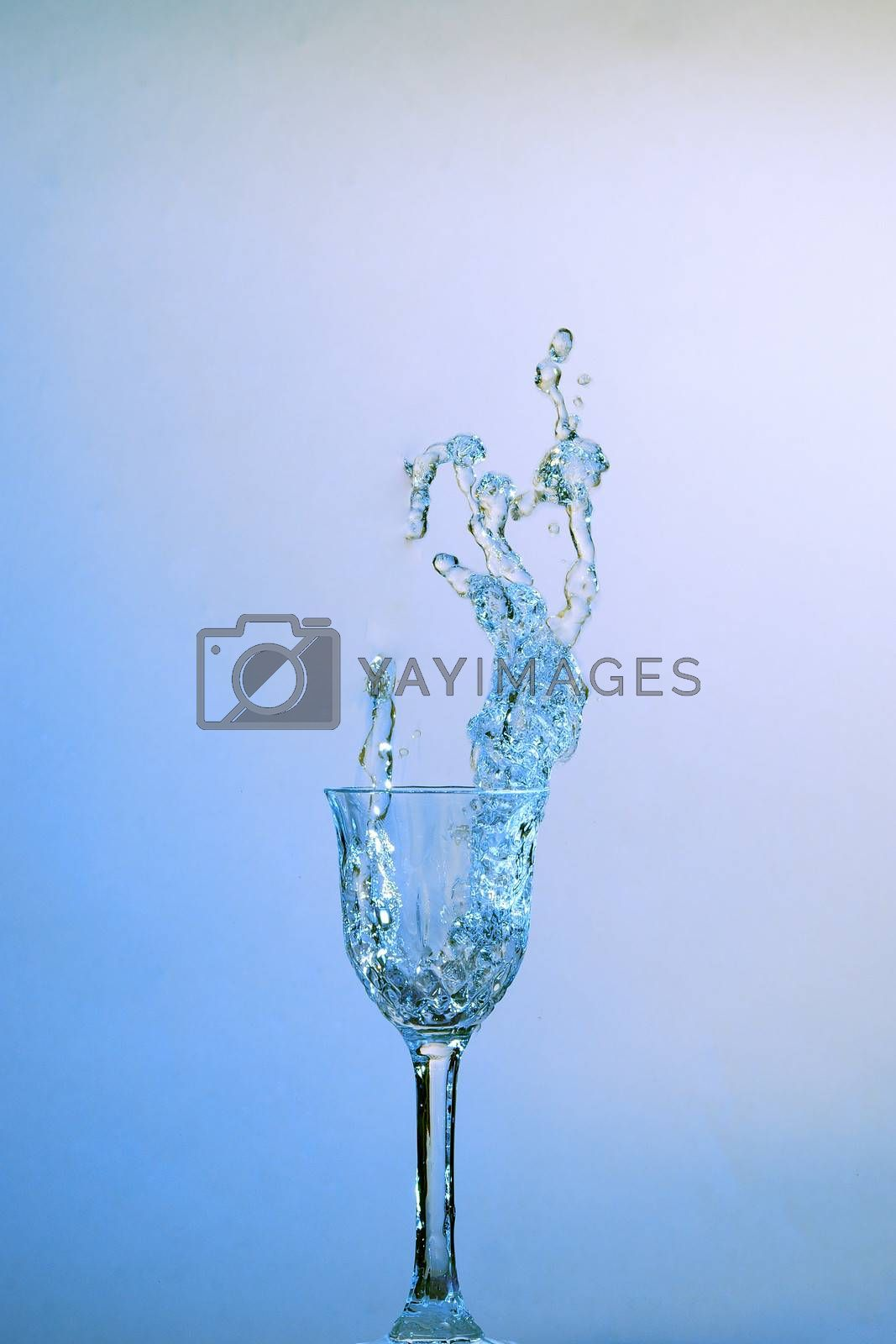 splashing in clear blue water glass with blue background