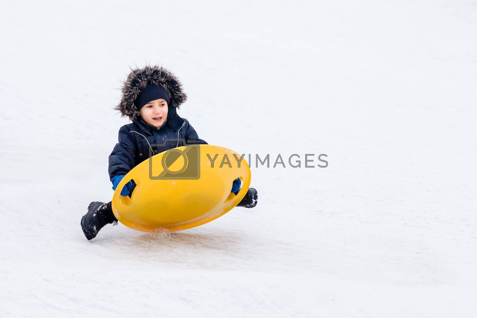 Boy on sleigh. Sledding at winter time