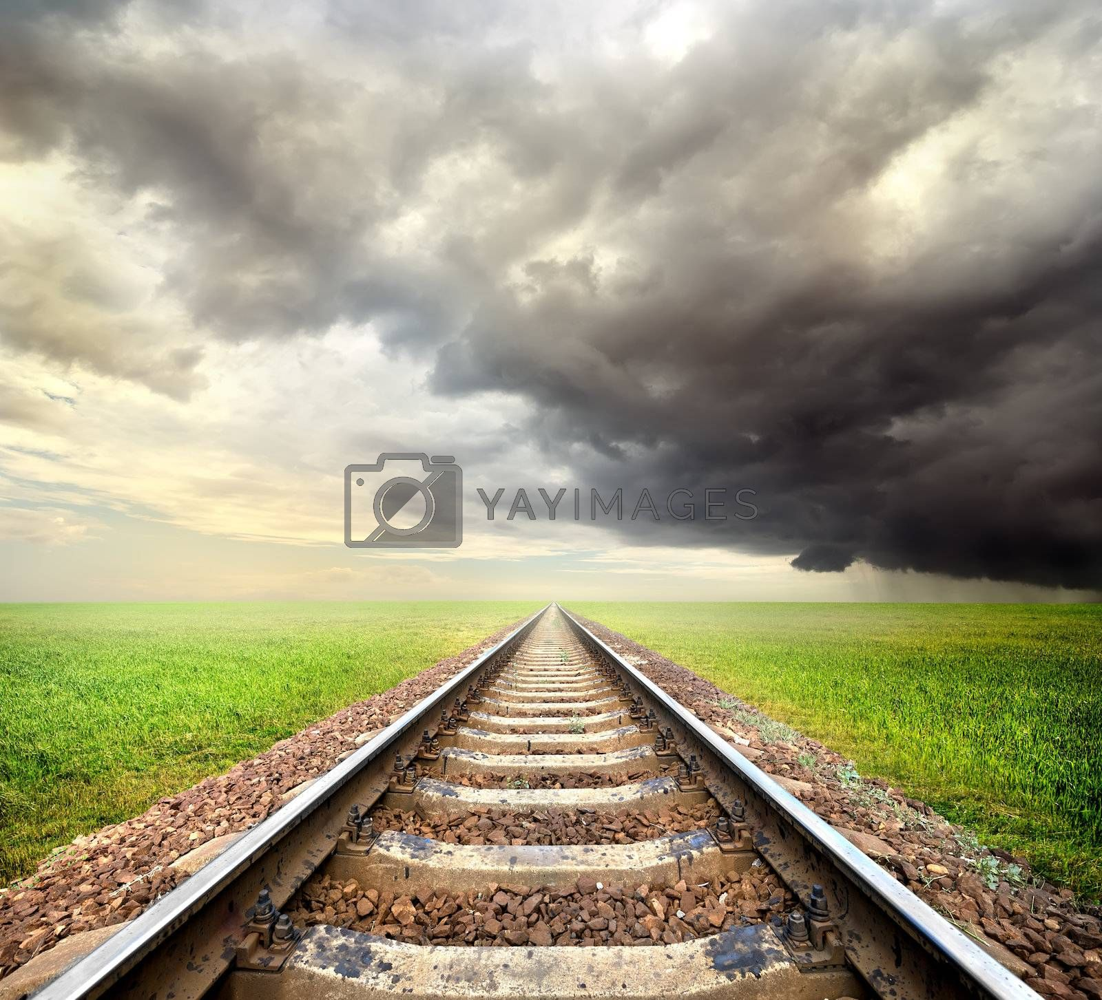 Railway in the field and storm clouds