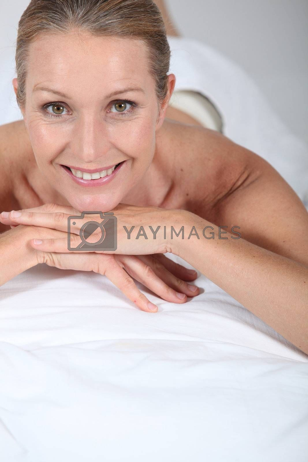 Blond woman laid on front awaiting massage by phovoir