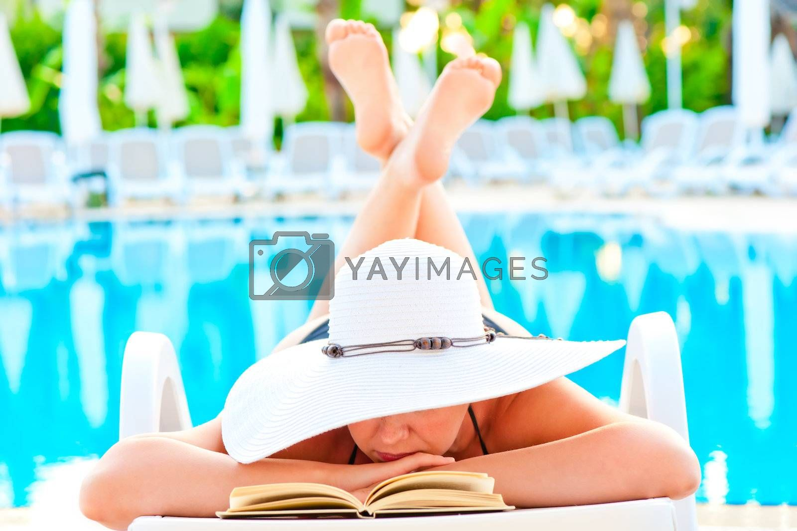 girl in a lounge chair near the pool and reading a romance novel by kosmsos111