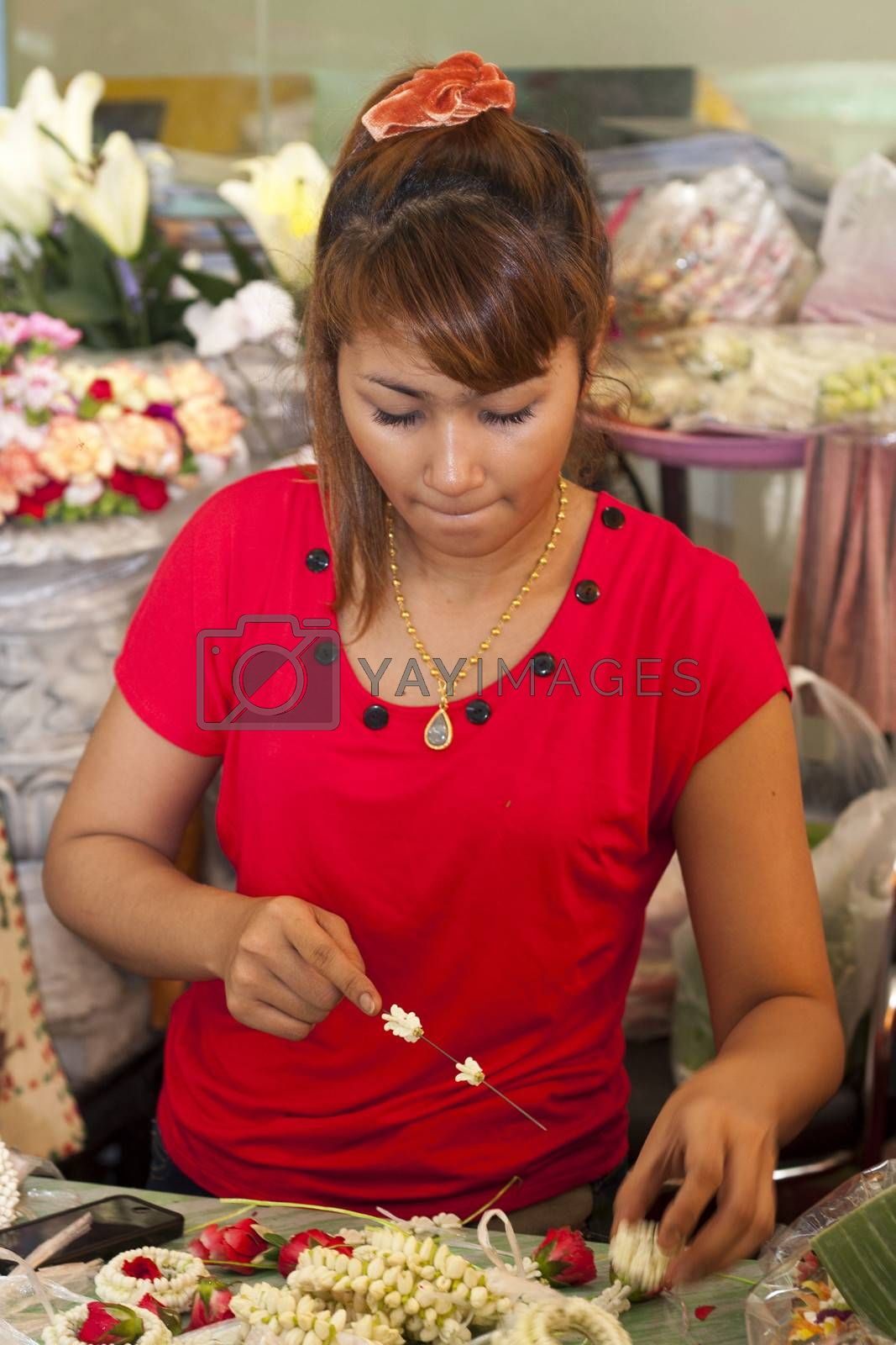 BANGKOK, THAILAND : OCT 12th: Girl making Buddhist garlands on Bangkok's flower market on October 12th 2012. Pak Khlong Talad is Bangkok's biggest flower market.