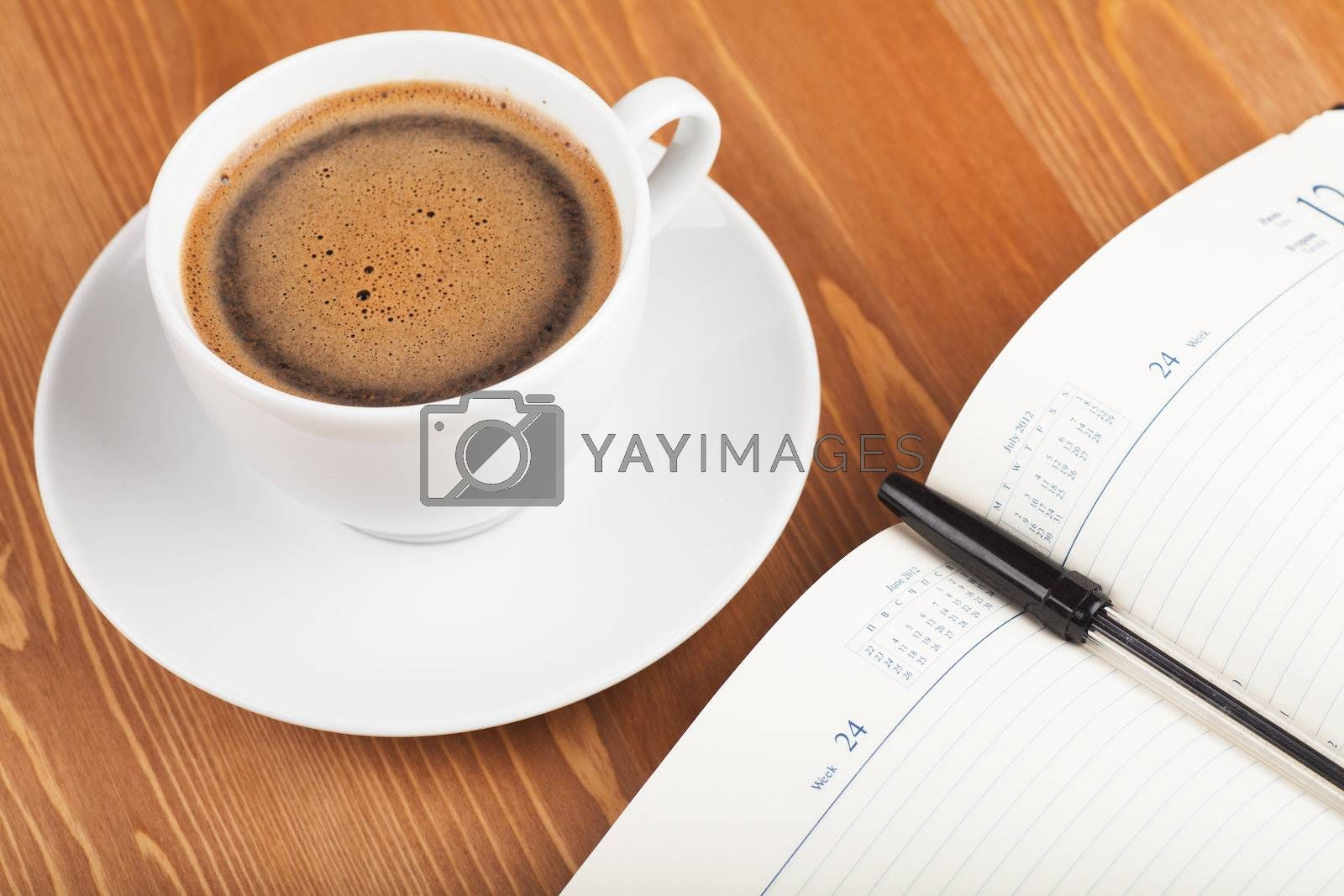 Notebook with pen and cup of coffee on a table. Top view
