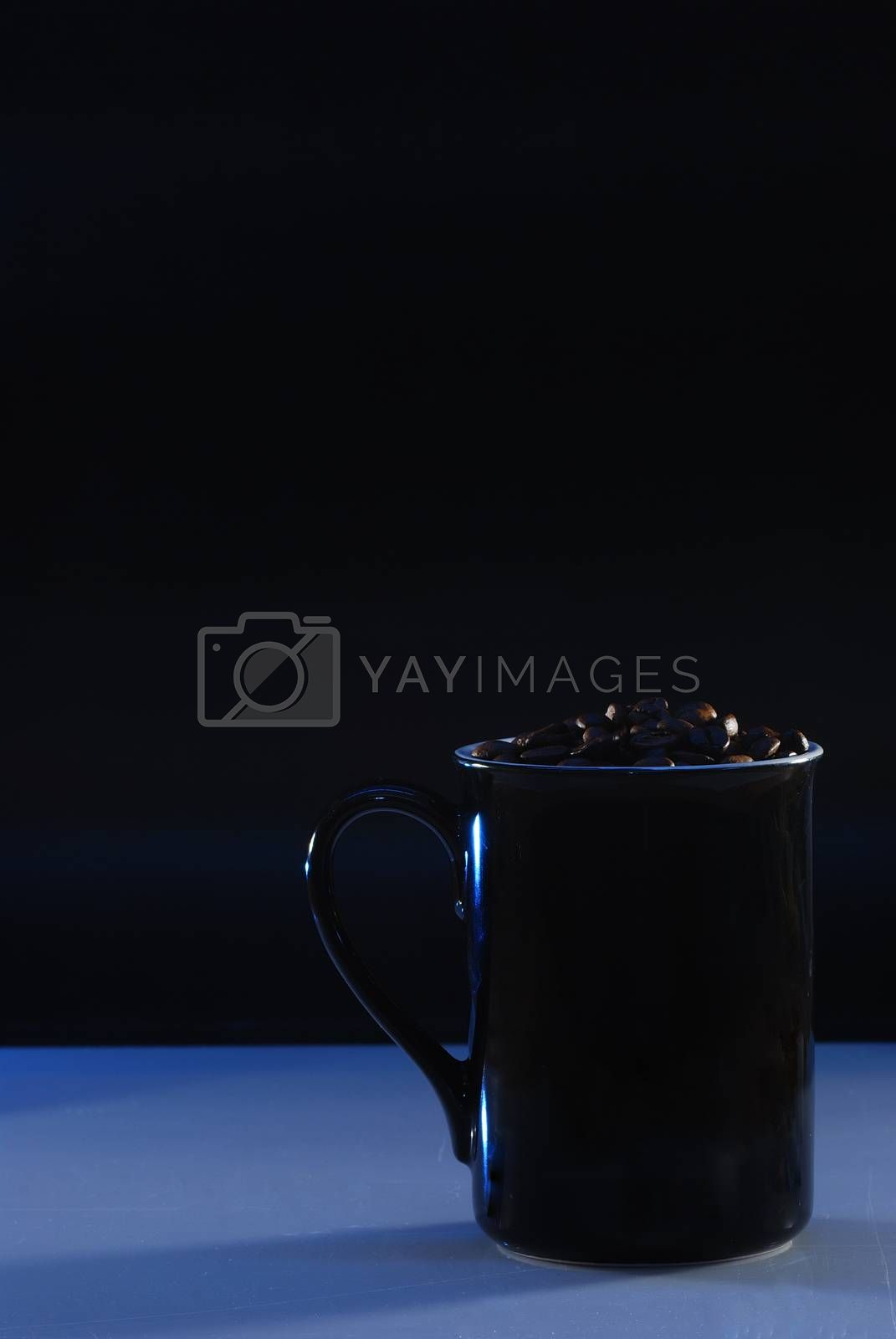 coffee cup with beans on blue surface and black background