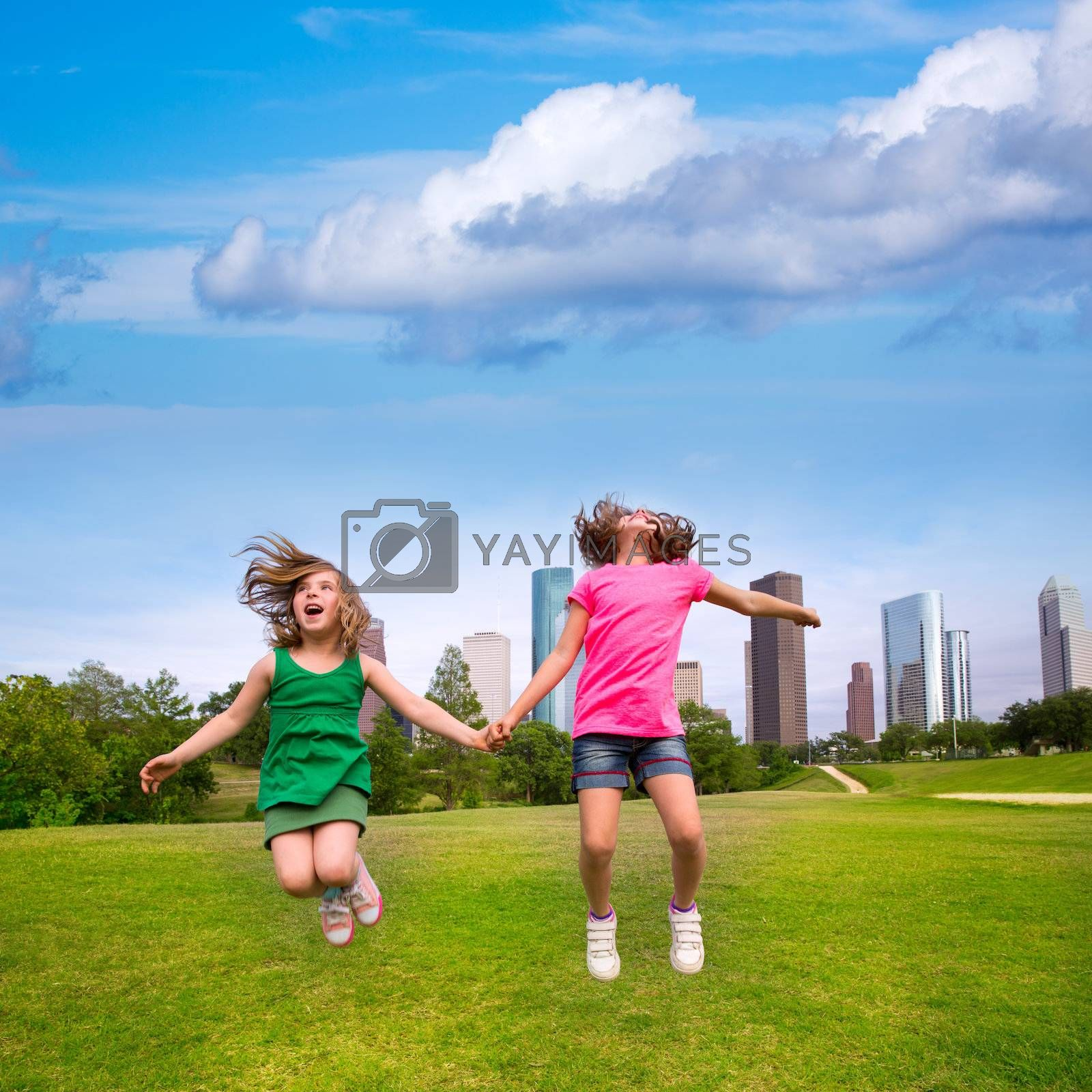 Two sister girls friends jumping happy holding hand in urban modern skyline on park lawn
