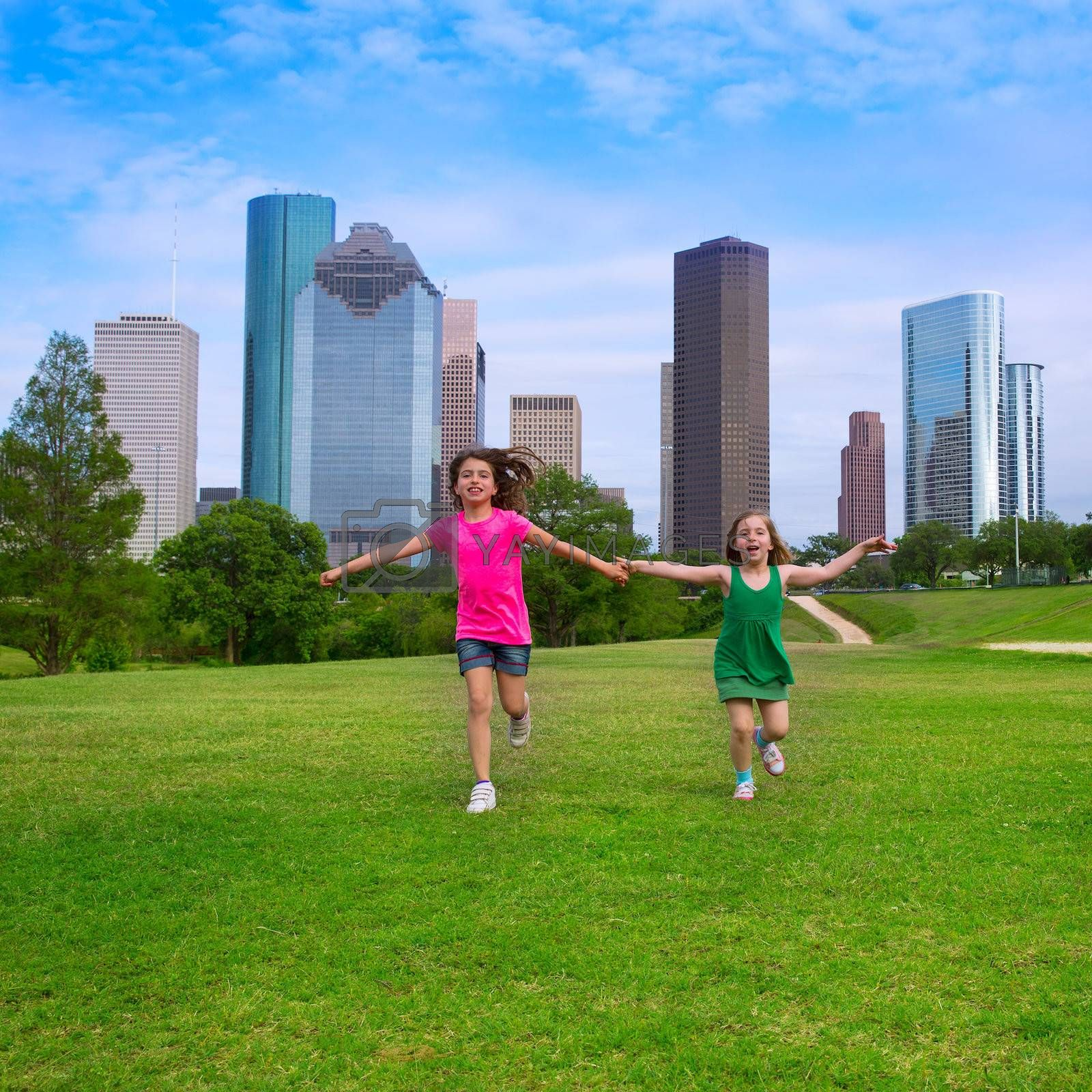 Two sister girls friends running holding hand in urban modern skyline on grass lawn