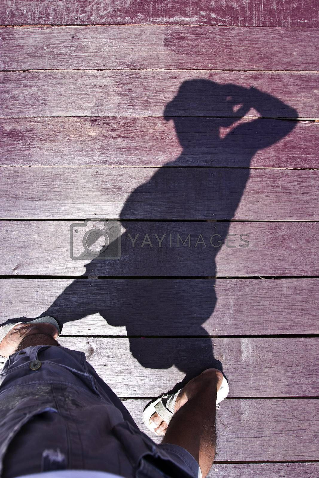 Human with the sunlight shadow on the wooden platform
