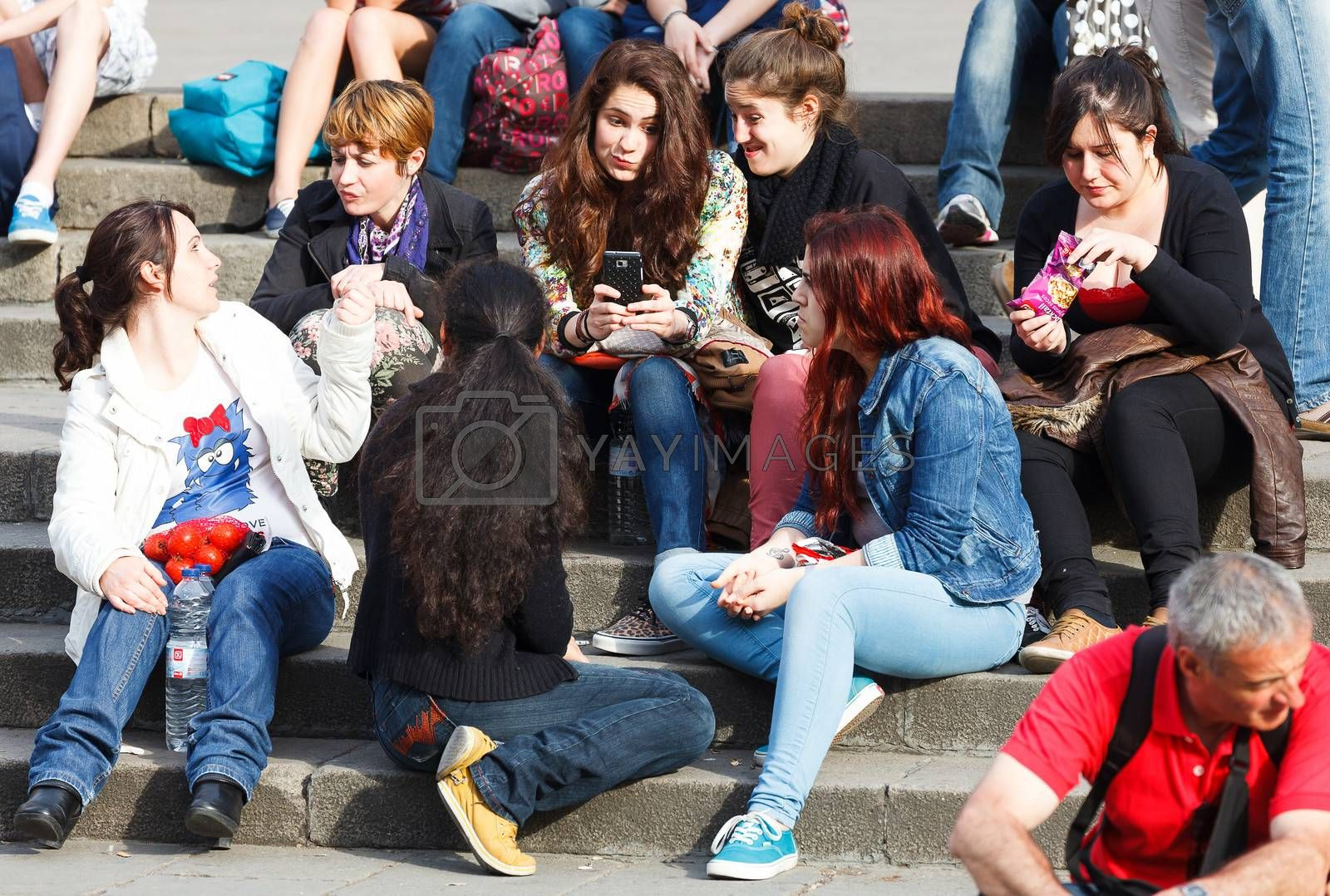 BARCELONA, SPAIN - APR 16: Company of young girls sitting on steps of Barcelona Cathedral. April 16, 2013 in Barcelona, Spain. This Cathedral, is the seat of the Archbishop of Barcelona