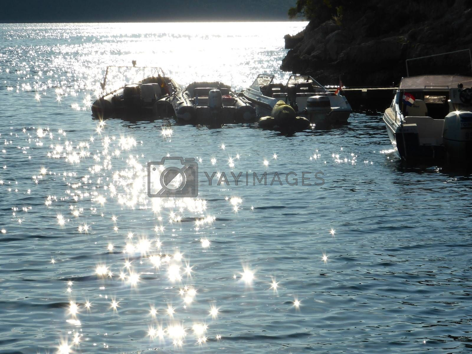 A beautiful sunny day on the crystal waters of the Adriatic Sea near Rovinj, Croatia. The sun is dazzling through romantic and peaceful reflexes on the quiet waves, while sleeping boats are resting on the background waiting for a fisher or a romantic couple taking a rest.