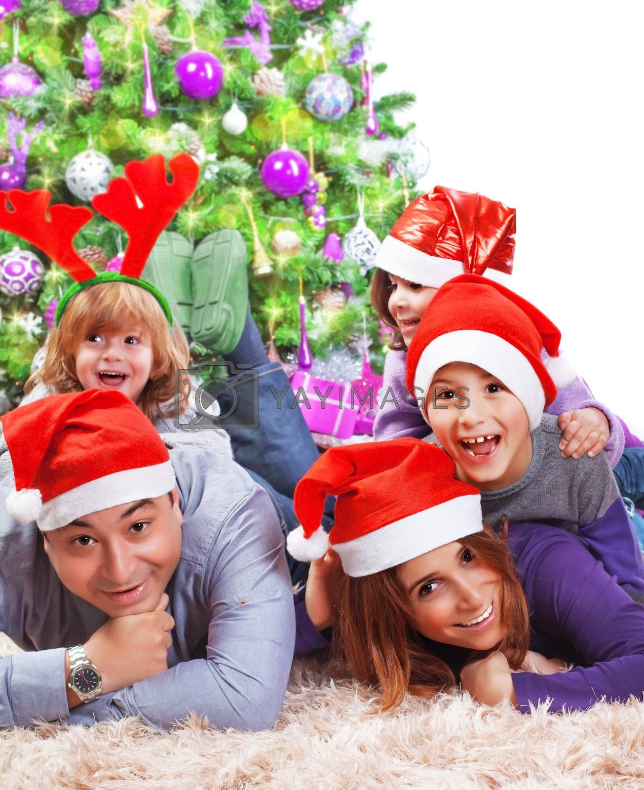Portrait of happy large family celebrating Christmas holidays at home, lying down near Xmas tree, wearing red Santa hat, New Year eve