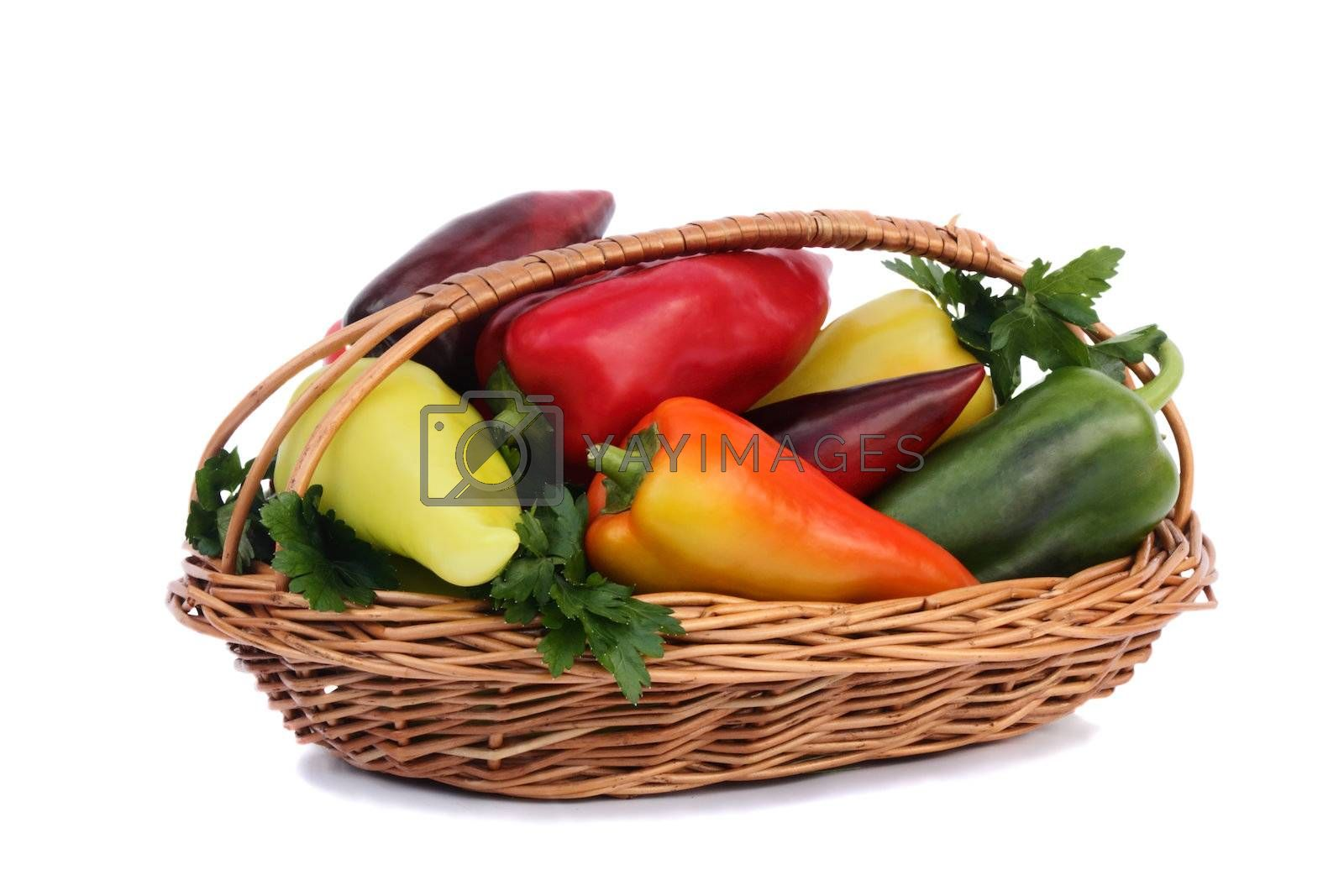 Wicker basket filled with ripe red, yellow, green peppers. Presented on a white background.