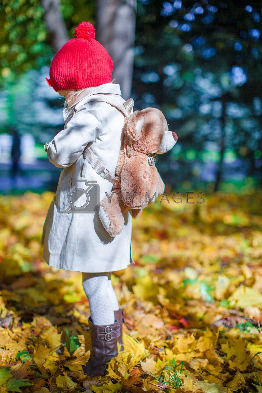 Little cute girl with a backpack-bear walks in the autumn forest on beautiful sunny day