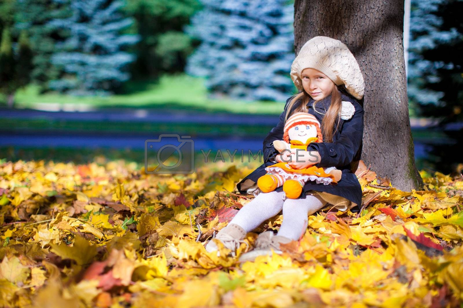 Pretty Fashion girl sits under a maple tree with doll on sunny autumn day