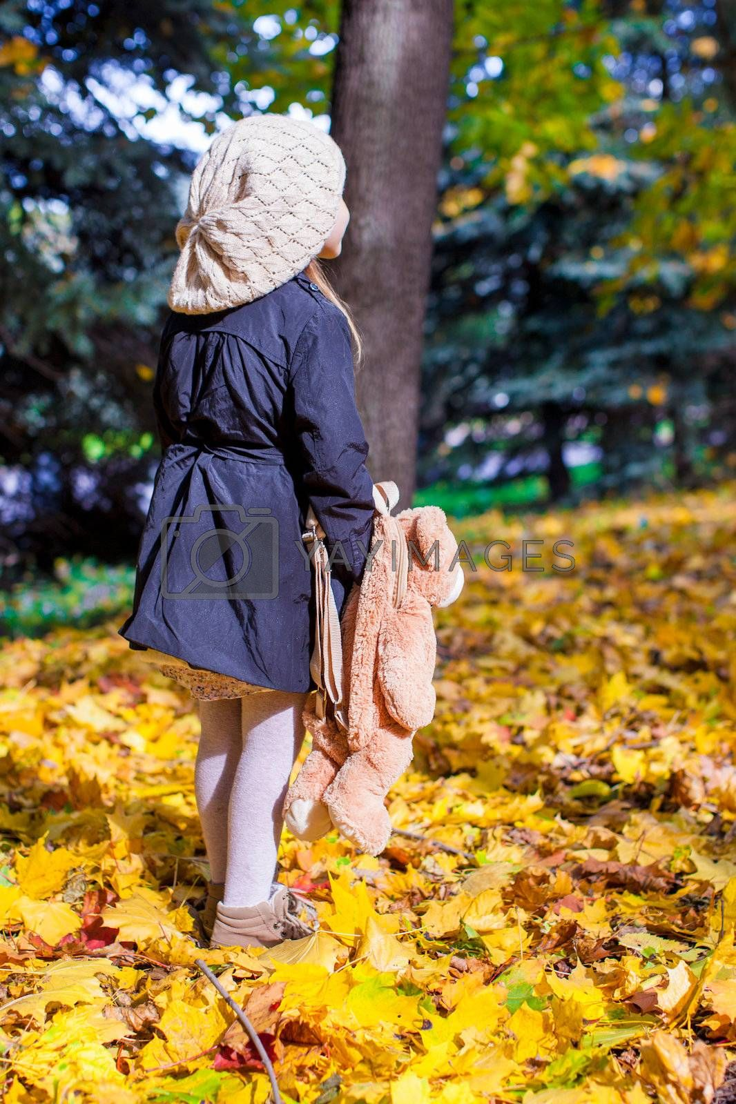Rear view of a charming little girl with a backpack-bear behind in the autumn sunny forest