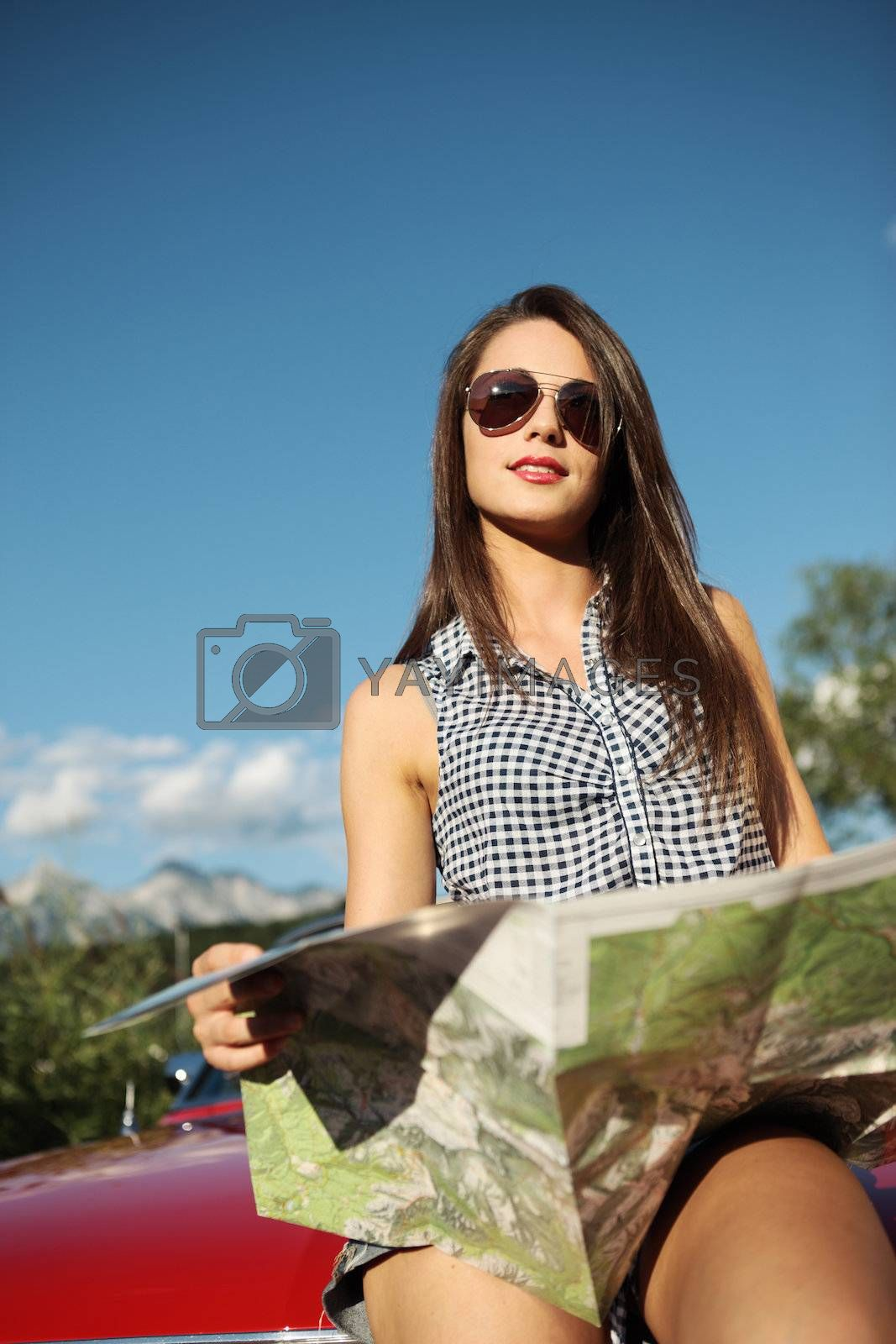 Young beautiful woman wearing sunglasses reading a roadmap
