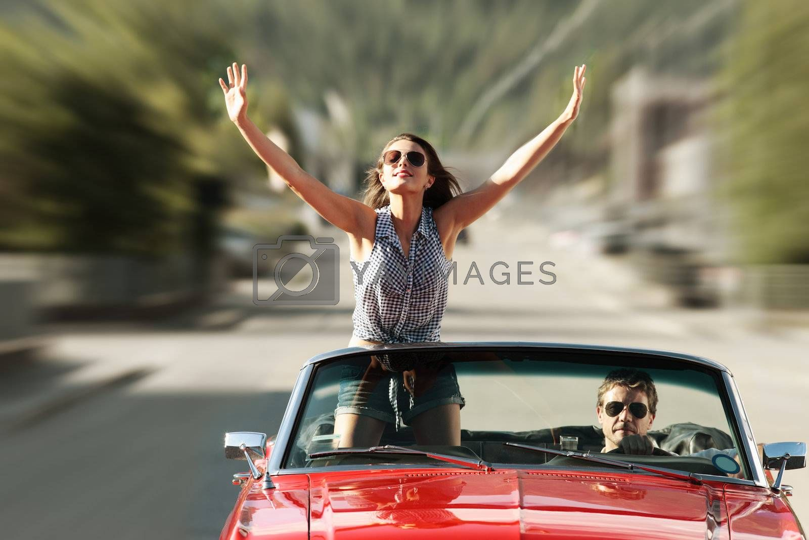 Happy young people in a convertible car